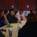 Students sitting at table eating lunch in cafeteria