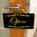 Black sign on a wooden door with gold lettering stating 'Open'.