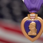 A Purple Heart metal in front of a blurred America flag.