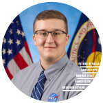 smiling student wearing dress shirt and tie with a NASA on the left breast, US and NASA flags in background
