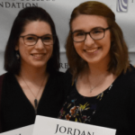 two women, smiling having jsut received a scholarship